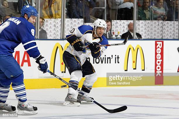 Andy McDonald of the StLouis Blues passes the puck against Niklad Hagman of the Toronto Maple Leafs during their NHL game at the Air Canada Centre...