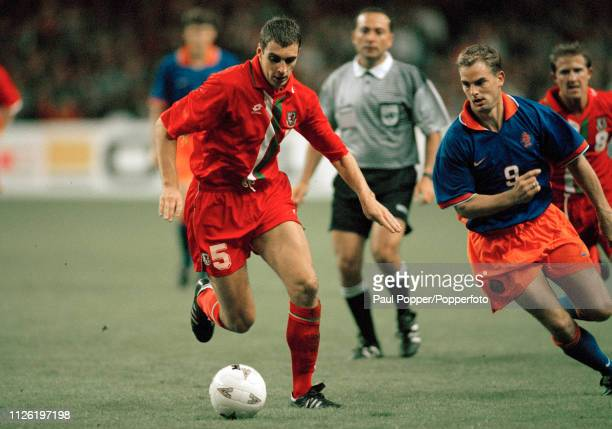 Andy Melville of Wales is watched by Frank de Boer of the Netherlands during a 1998 FIFA World Cup Qualifying match at the Cardiff Arms Park on...