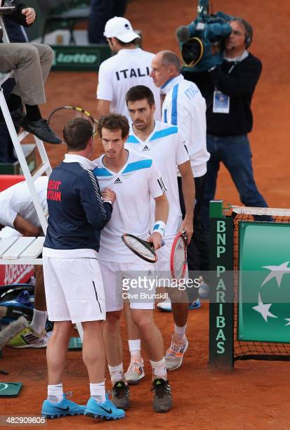 Andy Murray and Colin Fleming of Great Britain are congratulated by their team captain Leon Smith after their four set victory in the doubles third...