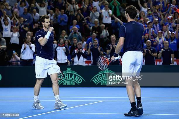 Andy Murray and Jamie Murray of Great Britain celebrate match point in the doubles match against Yasutaka Uchiyama and Yoshihito Nishioka of Japan on...
