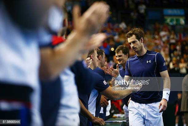 Andy Murray and Jamie Murray of Great Britain celebrate with teammates following their victory during the doubles match against Yoshihito Nishioka...