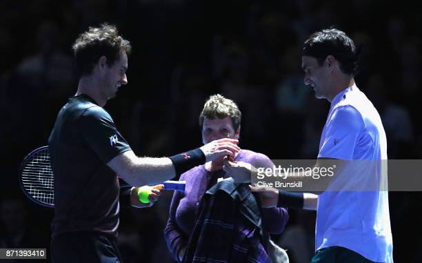 Andy Murray and Roger Federer sign a Kilt worn by Roger Federer during their match during Andy Murray Live at The Hydro on November 7 2017 in Glasgow...