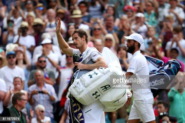 Andy Murray of Great Britain acknowledges the crowd as he walks off court alongside Benoit Paire of France after the Gentlemen's Singles fourth round...