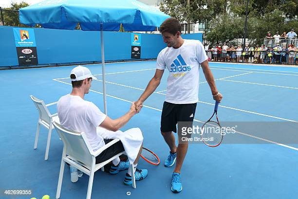Andy Murray of Great Britain and Daniel Vallverdu shake hands during a practice session on day three of the 2014 Australian Open at Melbourne Park on...