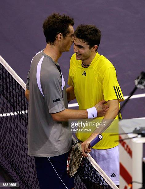 Andy Murray of Great Britain and Gilles Simon of France meet at the net after Murrays straight set victory during the final at the Madrid Masters...