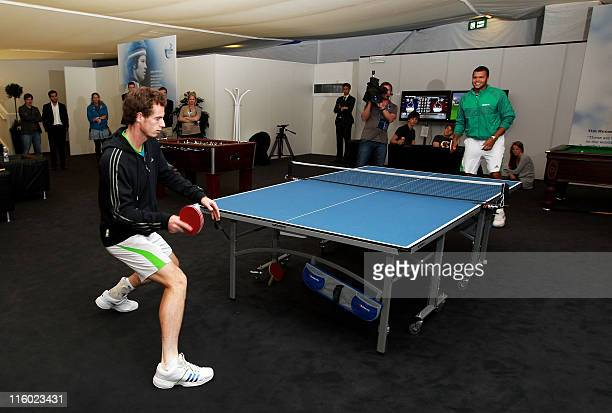 Andy Murray of Great Britain and JoWilfred Tsonga of France play table tennis in the players lounge due to the postponement of the final of the ATP...