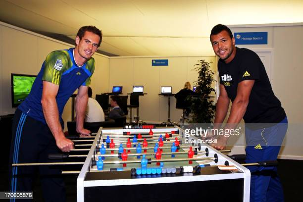 Andy Murray of Great Britain and JoWilfried Tsonga of France enjoy a game of Table Football as rain stops play ahead of the Men's Singles semi final...