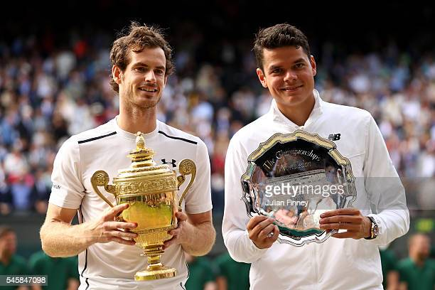 Andy Murray of Great Britain and Milos Raonic of Canada hold their trophies following the Men's Singles Final on day thirteen of the Wimbledon Lawn...