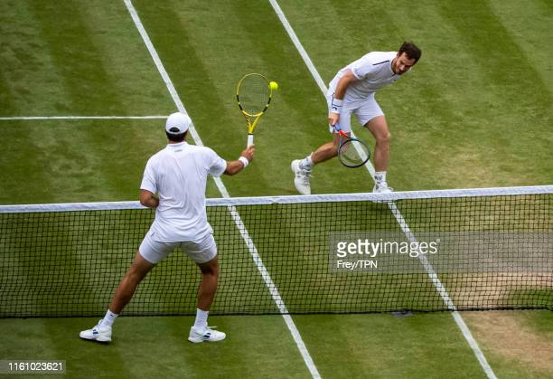 Andy Murray of Great Britain and Serena Williams in action against Fabrice Martin of France and Raquel Atawo of the United States in action in the...