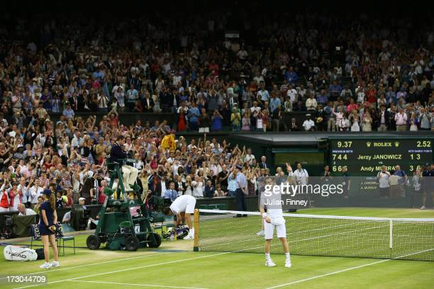 Andy Murray of Great Britain celebrates victory as Jerzy Janowicz of Poland prepares to leave Centre Court following their Gentlemen's Singles...