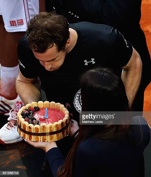 Andy Murray of Great Britain celebrates winning his match against Novak Djokovic of Serbia by blowing out a candle on a birthday cake which was...