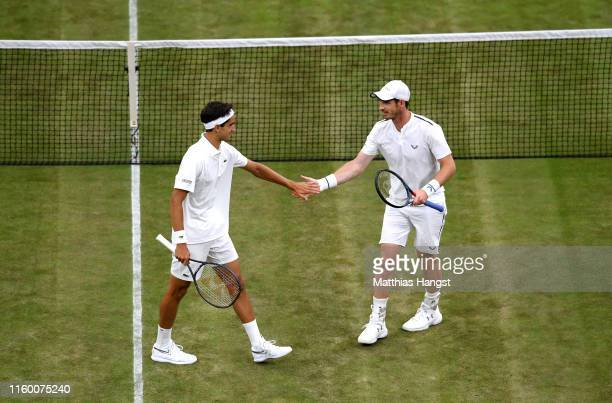 Andy Murray of Great Britain celebrates with playing partner Pierre-Hughes Herbert of France during their Men's Doubles first round match against...