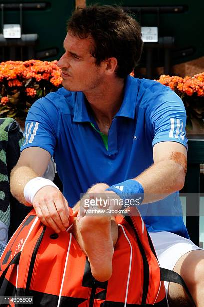 Andy Murray of Great Britain checks his foot during a break after picking up an injury during the men's singles round three match between Andy Murray...