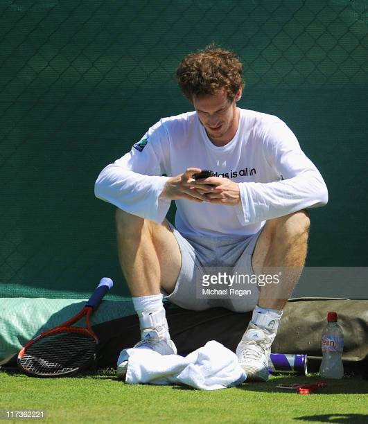 Andy Murray of Great Britain checks his mobile phone during a practice session during Middle Sunday of the Wimbledon Lawn Tennis Championships at the...