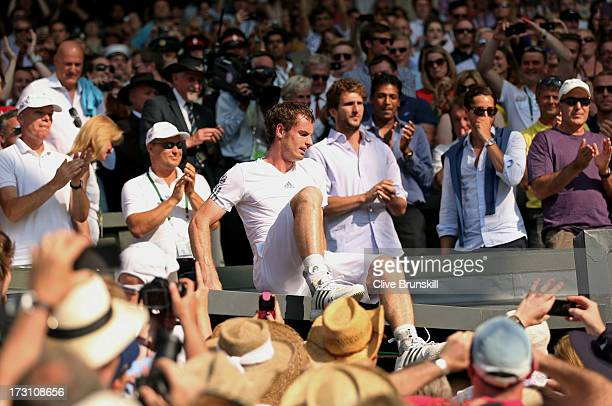 Andy Murray of Great Britain climbs down after celebrating in his player's box with friends family and members of his coaching team following his...