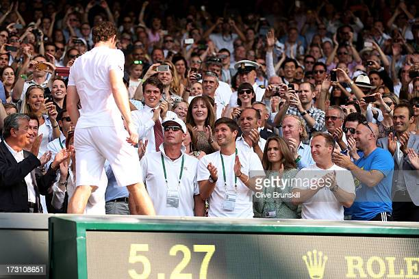 Andy Murray of Great Britain climbs into his player's box to celebrate with friends family and members of his coaching team following his victory in...