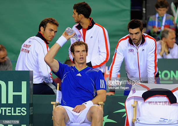 Andy Murray of Great Britain cools down as team mates Ross Hutchins James Ward and Colin Fleming look on against Gyorgy Balazs of Hungary during day...