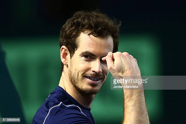 Andy Murray of Great Britain enquires about the score in the North London derby between Tottenham Hotspur and Arsenal during the doubles match...