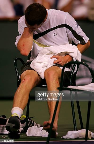 Andy Murray of Great Britain examines his elbow after falling and injuring his ankle in his quarterfinal match against Tommy Haas of Germany during...