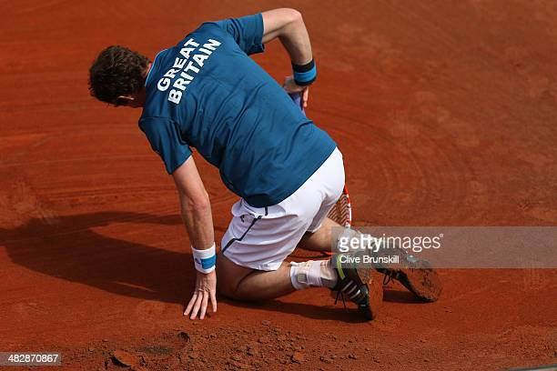 Andy Murray of Great Britain falls over against Andreas Seppi of Italy during day two of the Davis Cup World Group Quarter Final match between Italy...