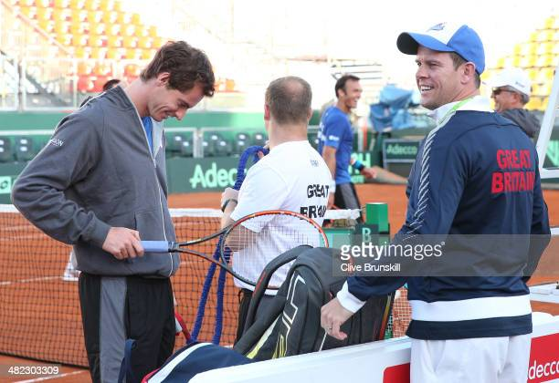 Andy Murray of Great Britain gets his racket ready for a late practice session watched by his team captain Leon Smith prior to the Davis Cup World...