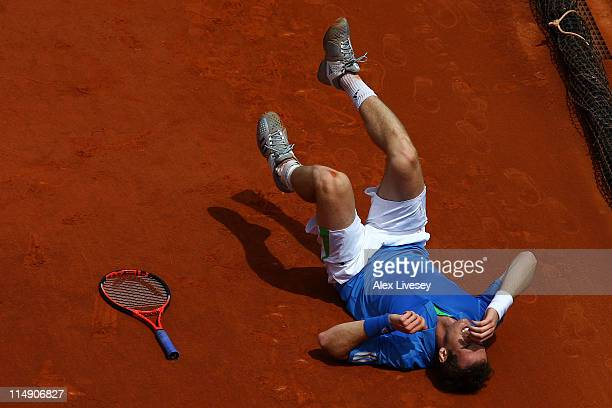 Andy Murray of Great Britain grimaces as he lies on the floor after injuring his foot during the men's singles round three match between Andy Murray...