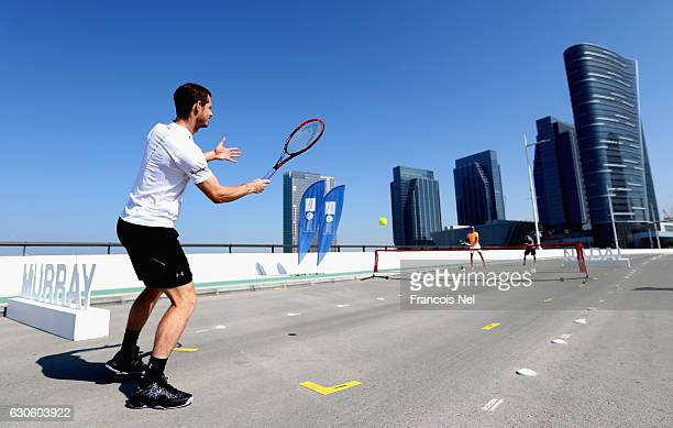 Andy Murray of Great Britain hits a return to Rafeal Nadal of Spain during the offical players launch of 2016 Mubadala Tennis Championship at Al...