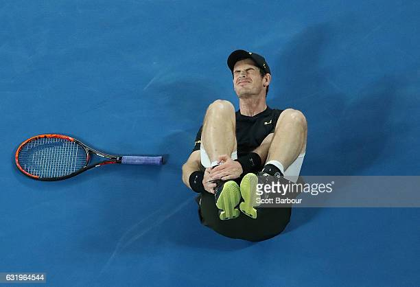 Andy Murray of Great Britain holds his ankle after he fell over in his second round match against Andrey Rublev of Russia on day three of the 2017...