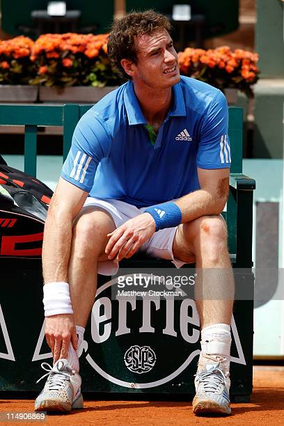 Andy Murray of Great Britain holds his ankle during a break after picking up an injury during the men's singles round three match between Andy Murray...