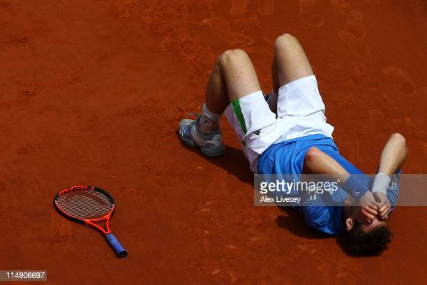 Andy Murray of Great Britain holds his head in his hands after injuring his ankle during the men's singles round three match between Andy Murray of...