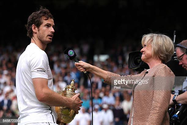 Andy Murray of Great Britain holds the trophy as he is interviewed by Sue Barker following victory in the Men's Singles Final against Milos Raonic of...