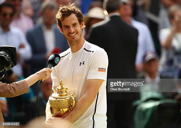 Andy Murray of Great Britain holds the trophy as he is interviewed following victory in the Men's Singles Final against Milos Raonic of Canada on day...