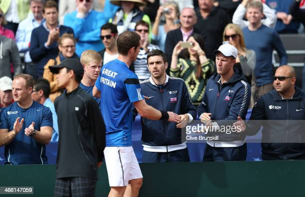 Andy Murray of Great Britain is congratulated by his team mates after his straight sets victory against Donald Young of the United States in the...
