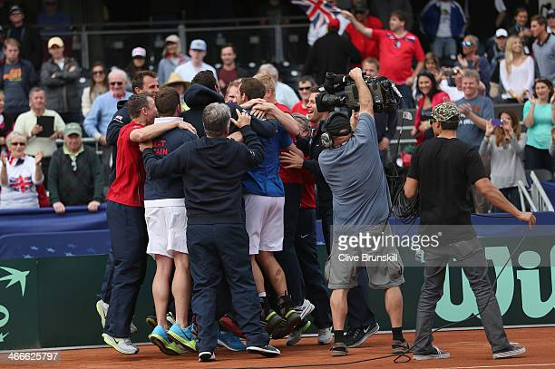 Andy Murray of Great Britain is hugged by team mates Dominic InglotJames Ward and Kyle Edmund after his four set victory against Sam Querrey of the...