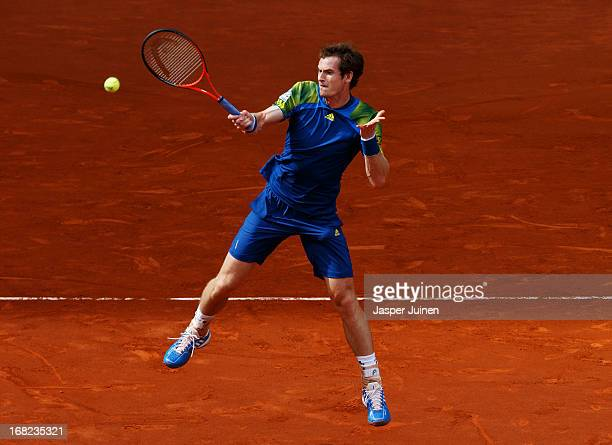Andy Murray of Great Britain jumps to play a backhand to Florian Mayer of Germany during his match on day four of the Mutua Madrid Open tennis...