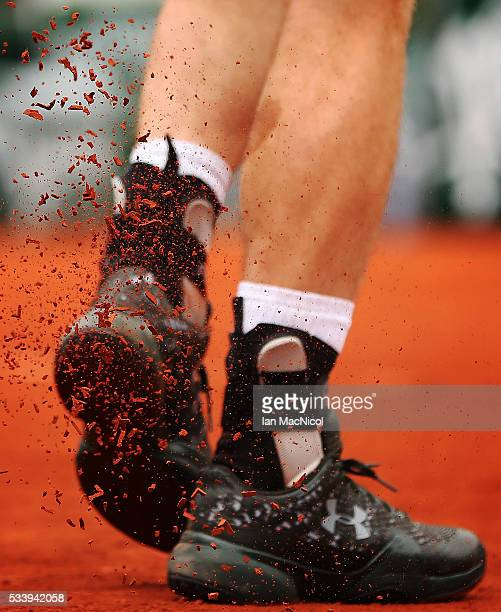 Andy Murray of Great Britain knocks the clay from the sole of his shoe during the Men's Singles first round match against Radek Stepanek of the Czech...