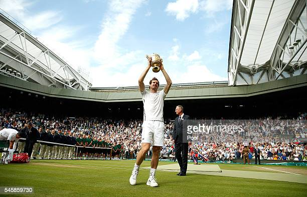 Andy Murray of Great Britain lifts the trophy following victory in the Men's Singles Final against Milos Raonic of Canada on day thirteen of the...