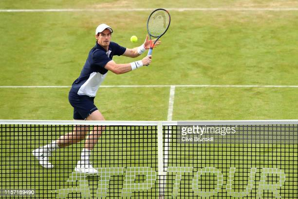 Andy Murray of Great Britain, partner of Feliciano Lopez of Spain plays a backhand shot at the net during his First Round Doubles match against Juan...