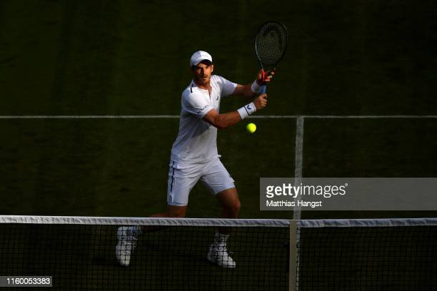 Andy Murray of Great Britain partner of PierreHughes Herbert of France plays a backhand at the net during their Men's Doubles first round match...