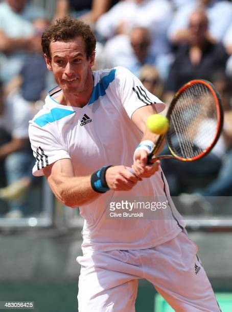 Andy Murray of Great Britain plays a backhand during his straight sets defeat in the fourth rubber by Fabio Fognini of Italy during day three of the...