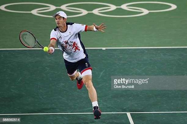 Andy Murray of Great Britain plays a forehand during the mixed doubles first round match against Carla Suarez Navarro of Spain and David Ferrer of...