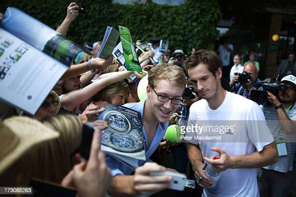 Andy Murray of Great Britain poses for photographs with fans after a practice session on day twelve of the Wimbledon Lawn Tennis Championships at the...