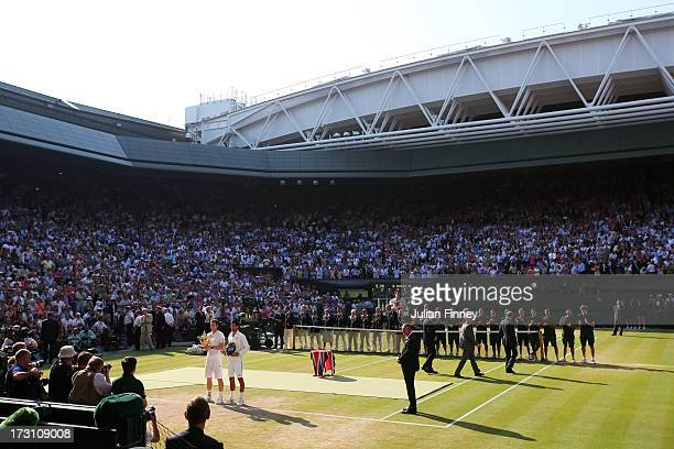 Andy Murray of Great Britain poses on Centre Court with the Gentlemen's Singles Trophy next to Novak Djokovic of Serbia following his victory in the...