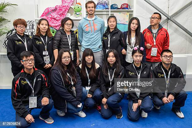 Andy Murray of Great Britain poses with staff members at the Offical Merchandise Booth on day six of the 2016 China Open at the China National Tennis...