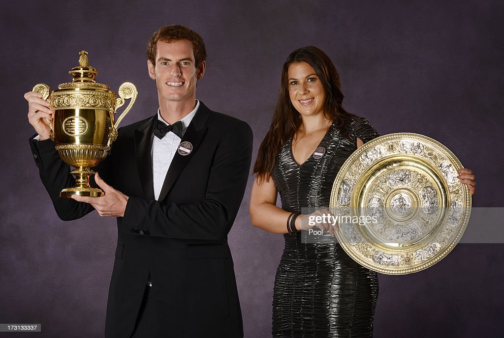 Andy Murray of Great Britain poses with the Gentlemen's Singles Trophy and Marion Bartoli of France (R) poses with the Venus Rosewater Dish trophy at the Wimbledon Championships 2013 Winners Ball at InterContinental Park Lane Hotel on July 7, 2013 in London, England.