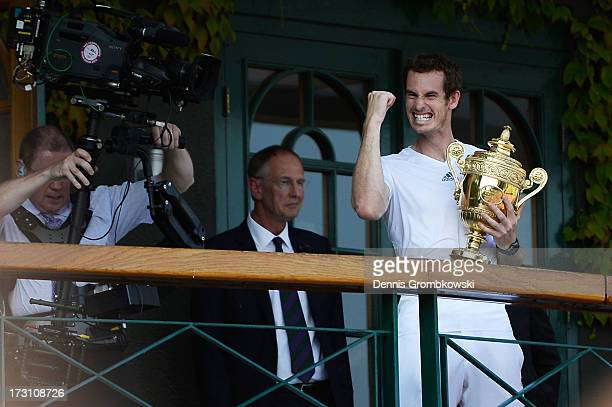 Andy Murray of Great Britain punches the air on the Centre court balcony as he holds the Gentlemen's Singles Trophy following his victory in the...