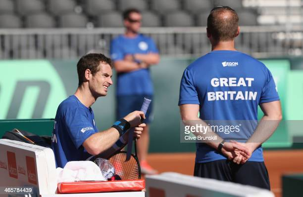 Andy Murray of Great Britain puts a new grip on his racket watched by fitness trainer Matt Little during a practice session watched prior to the...