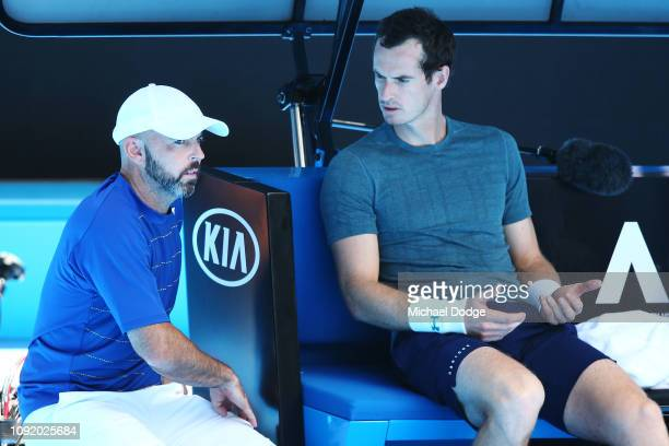 Andy Murray of Great Britain reacts next to coach Jamie Delgado after pulling out of his practice match against Novak Djokovic of Serbia ahead of the...