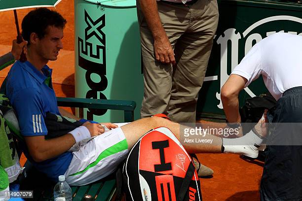 Andy Murray of Great Britain receives assistance during a break after injuring his foot during the men's singles round three match between Andy...