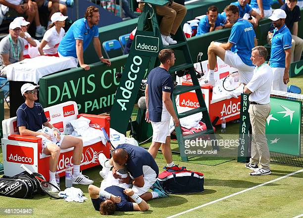 Andy Murray of Great Britain receives medical help in match with Jamie Murray against Nicolas Mahut and Jo-Wilfried Tsonga of France in the doubles...